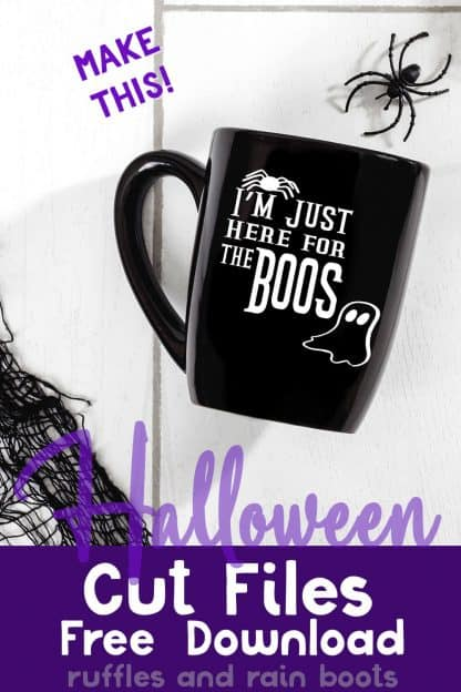 black coffee mug on white wood background decorated wtih free Just here for the Boos SVG from Ruffles and Rain Boots with text which reads Halloween cut files free download