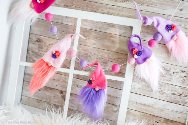 horizontal image of pinks and purples with gnomes with pink fur and hats and purple gnome hats and fur with felt wool balls