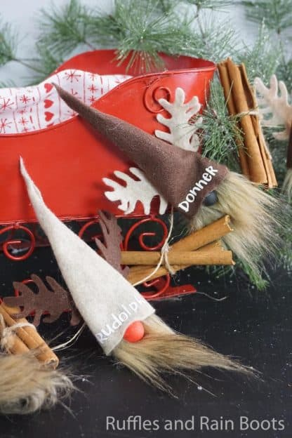 diy Christmas gnomes garland on black background with a red sleigh and greenery