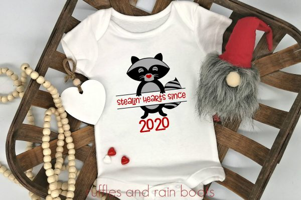 close up of baby onesie Valentines raccoon svg for stealin hearts on a farmhouse background