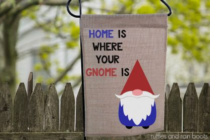 close up of a gnome garden flag on a wrought iron pole hanging in front of a fence made with gnome svg