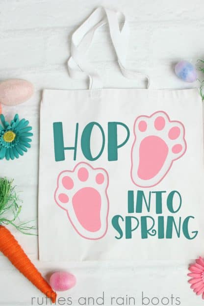 close up of Easter svg on tote bag with bunny paws and hop into spring in a playful teal text
