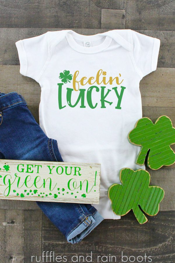 vertical image of wood background with white t shirt and jeans green shamrock and feelin lucky svg for cricut and silhouette