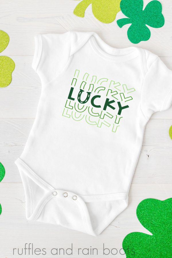 adorable onesie with lucky svg for cricut and silhouette on white background with shamrocks