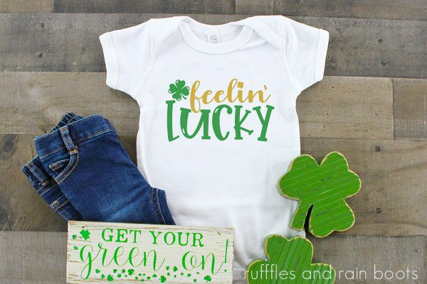 horizontal image of feelin lucky svg in gold and green for cricut on white t shirt with shamrock background