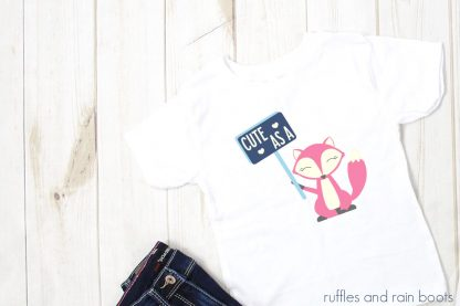 horizontal image of child white t shirt with pink and blue valentine fox svg on it holding a sign that says cute as a fox