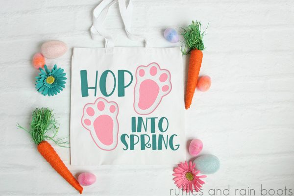 hop into spring svg placed on Easter tote bag on white wood background with craft flowers and carrots