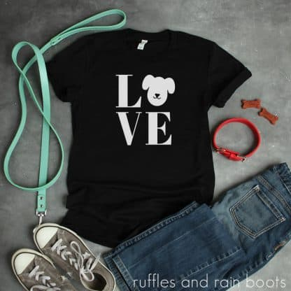 white dog love svg on black t shirt on concrete background with dog leash and collar