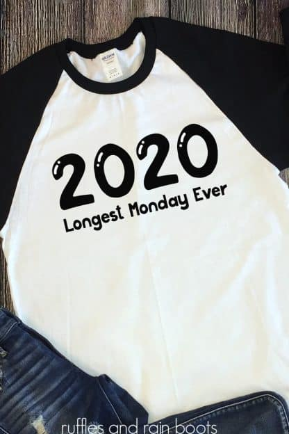 2020 svg with longest Monday ever cut file in black on white and black raglan t shirt on wood background
