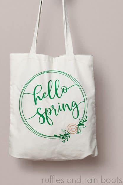 hello spring svg with wreath and flower on canvas tote bag and peach wall