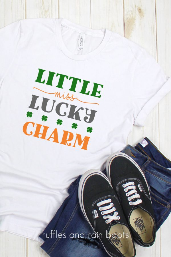 close up of little miss lucky charm cut file on white t shirt with black tennis shoes and jeans on white background