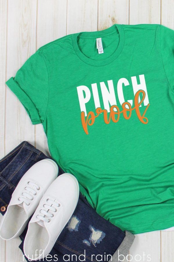 green t shirt on white wood background with pinch proof svg in white and green