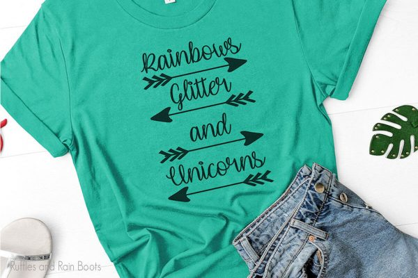 rainbows glitter and unicorns svg with arrows laying on a white table with blue jeans and sandals