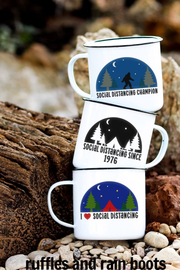three camp mugs with social distancing svg designs on them in front of wood in the forest and a pebble beach