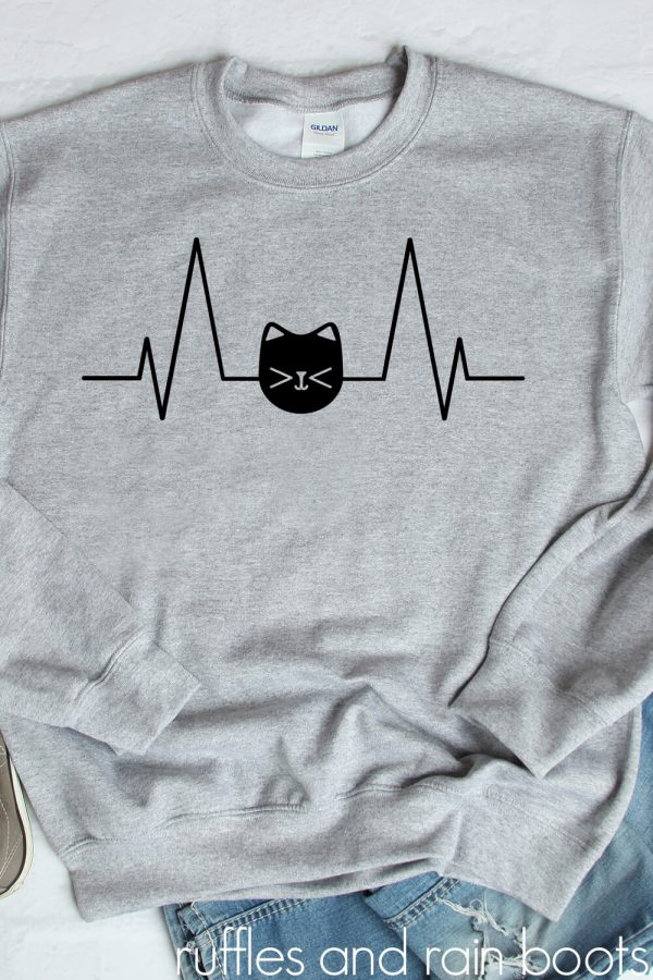 black cat heartbeat svg in vinyl on gray sweatshirt on white background with jeans