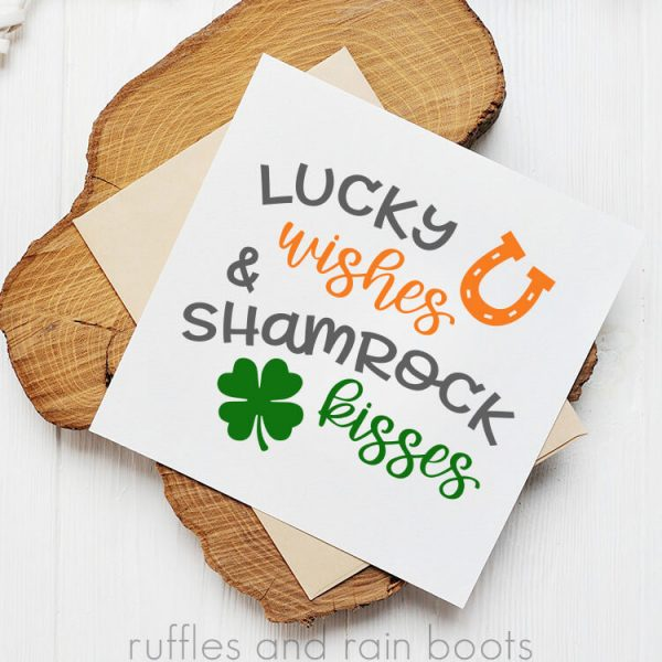 st patricks day card with svg on white card stock stacked on an envelope and wood plank