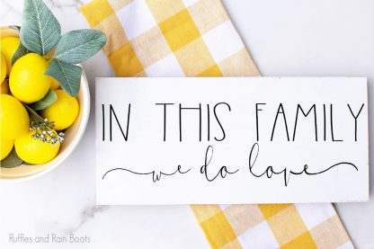 In This Family We Do Love SVG For cricut or silhouette on a wood sign for farmhouse wall art