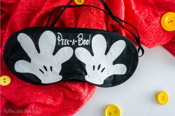 Mickey Hands Eye Mask on a table with yellow buttons and red linen