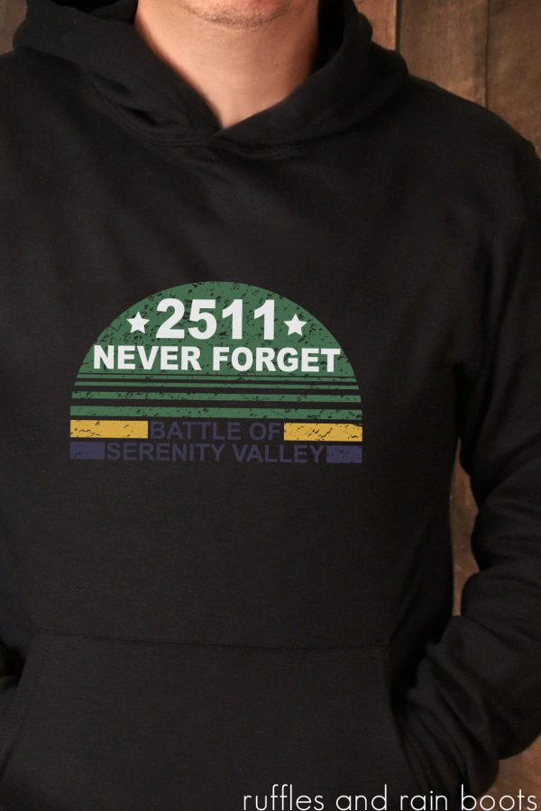 man in black hoodie with distressed battle of serenity svg made with Cricut machine in green gold and eggplant vinyl