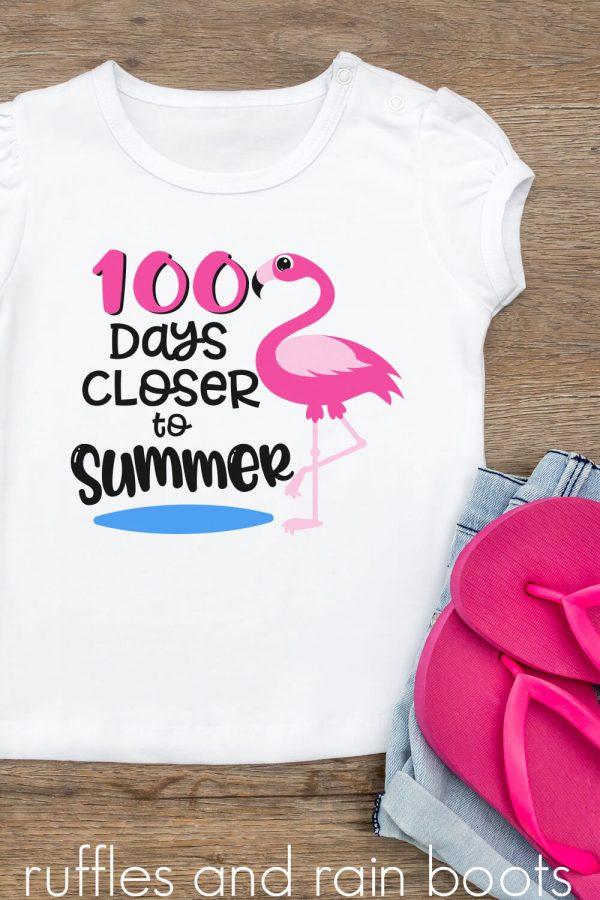 kids shirt laying on a wood table featuring a 100 days closer to summer svg with flamingo on t shirt