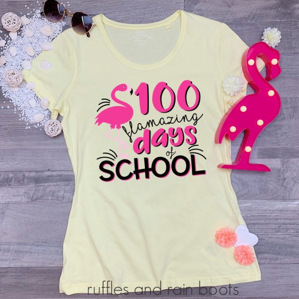 teacher shirt laying on a table featuring a 100 days of school flamingo svg cut file for cricut silhouette vinyl