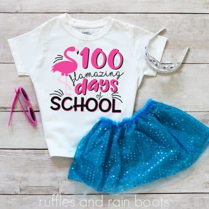 kids shirt laying on a table featuring a 100 flamazing days of school cut file flamingo svg