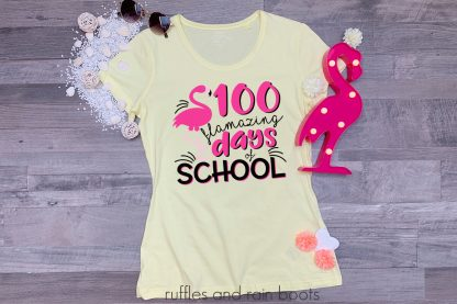 teacher shirt laying on a table featuring a 100 flamazing days of school flamingo svg