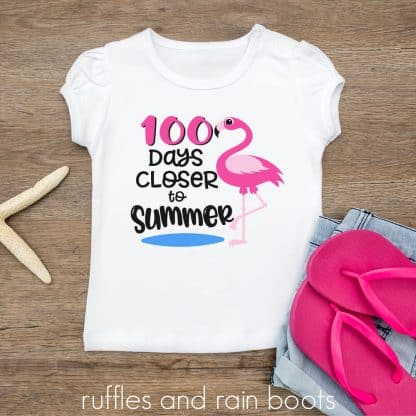 t-shirt laying on a wood table featuring a adorable flamingo school svg 100 days