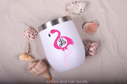 circle monogram flamingo cut file svg set on a stemless wine glass tumbler laying in the sand