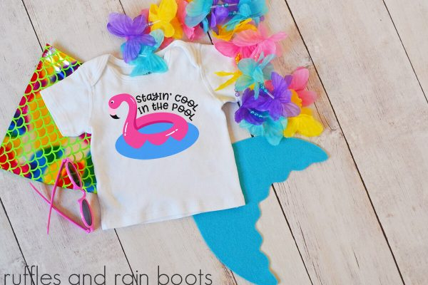 flamingo cut file for stayin cool in the pool svg on a kids tshirt laying on a table with a pool toy