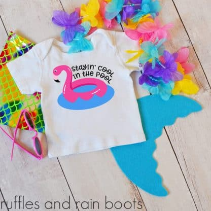 flamingo floatie SVG on a t-shirt laying on a table with a kids pool toy