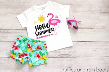 flamingo hello summer svg for cricut on a tshirt laying on a table with floral shorts