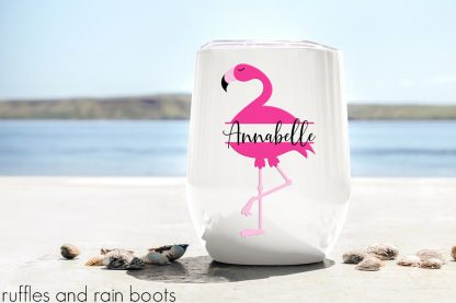 flamingo svg monogram with split monogram style for clipart and cut files on a stemless wine glass sitting on the beach