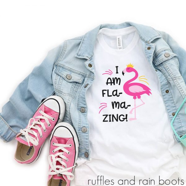 kids t-shirt laying on a table with accessories featuring a fun flamingo motivational svg for kids flamazing