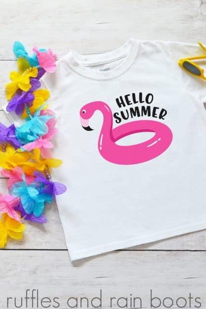 fun t shirt idea hello summer flamingo pool float svg for cricut on a kids shirt laying on a table with kids summer toys