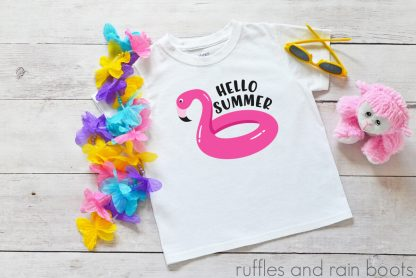 hello summer flamingo pool float svg for cricut silhouette clipart on a kids shirt laying on a table with some toys