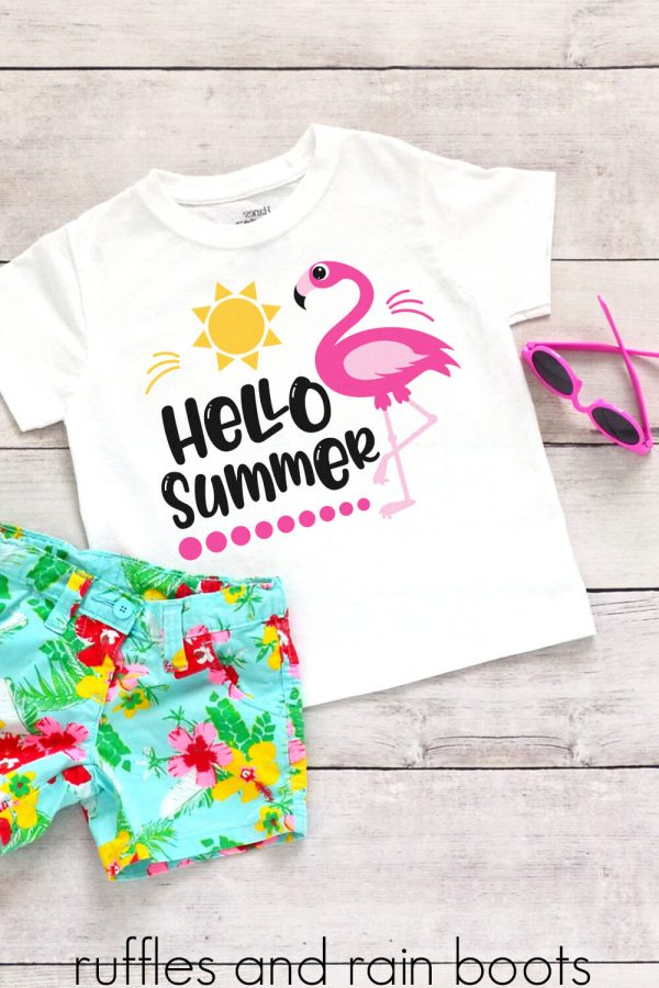 hello summer flamingo svg for cricut silhouette on a kids shirt laying on a table with floral shorts