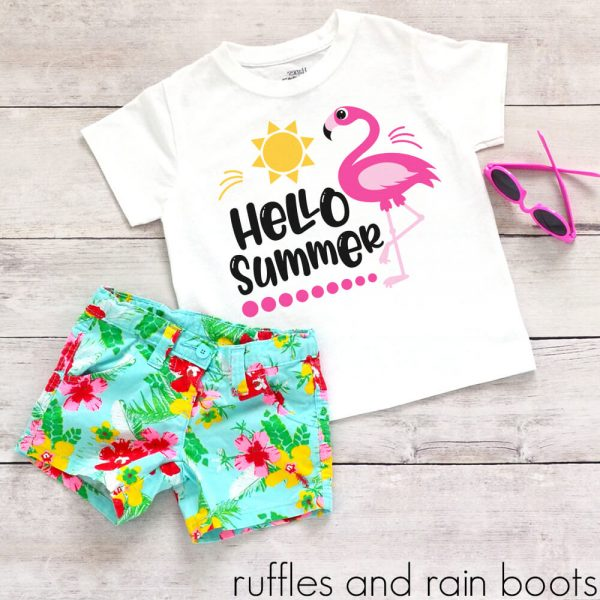 hello summer flamingo svg pool sunshine cut file on a kids t-shirt laying on a table with floral shorts