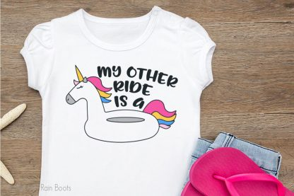 tshirt laying on a wood table featuring My Other Ride is a Unicorn Floatie unicorn SVG File Set For summer crafting