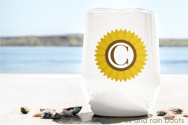 stemless wine glass tumbler sitting on the beach featuring a Sunflower Monogram sublimation file