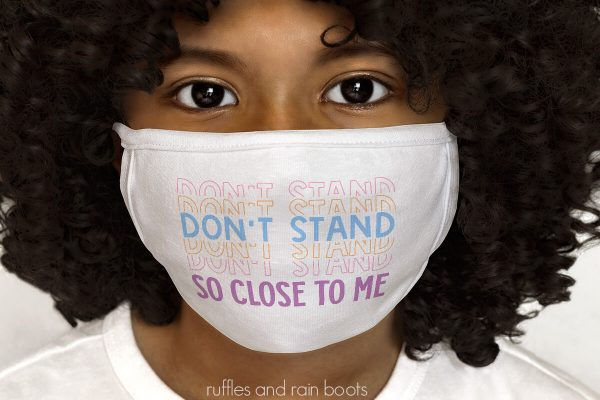 close up photo of small child with white face covering and the don't stand so close to me face mask svg in rainbow colors