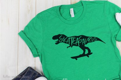 Skateasaurus Skateboard cut file on a green t-shirt laying on a table