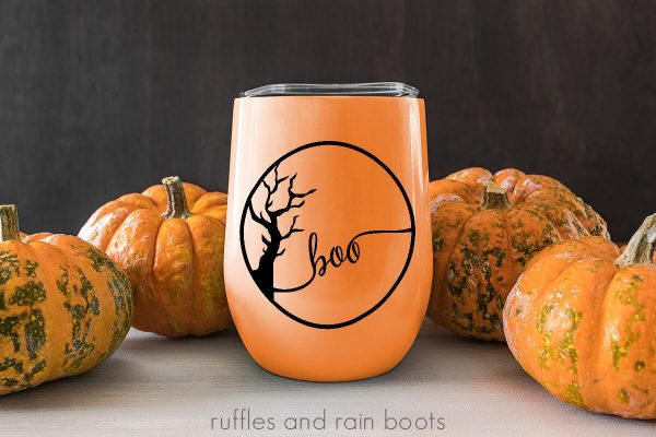 boo with spooky tree design in black on orange mug with pumpkin and wood background