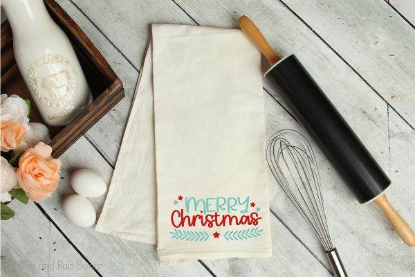 laurel and stars merry christmas cut file on a kitchen towel on a table