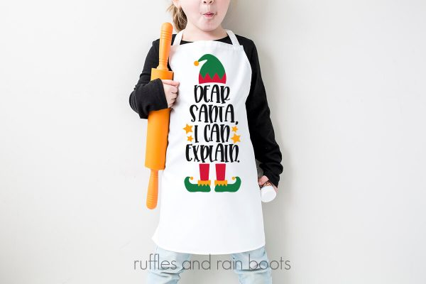 horizontal image of child in apron against white wall with Christmas SVG that says Dear Santa I can explain
