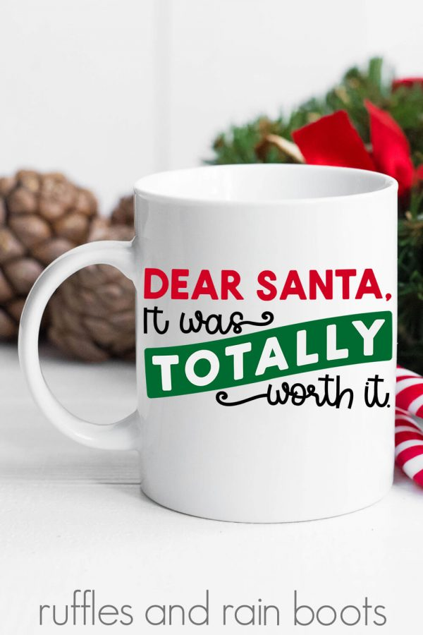white mug on holiday background with pinecones and greenery with red white and black Dear Santa SVG