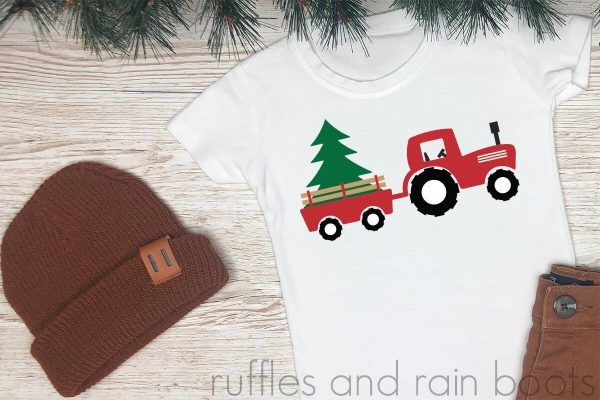 white wood background with brown hat and pants featuring a white t shirt with a red Christmas tractor cut file placed on top in vinyl