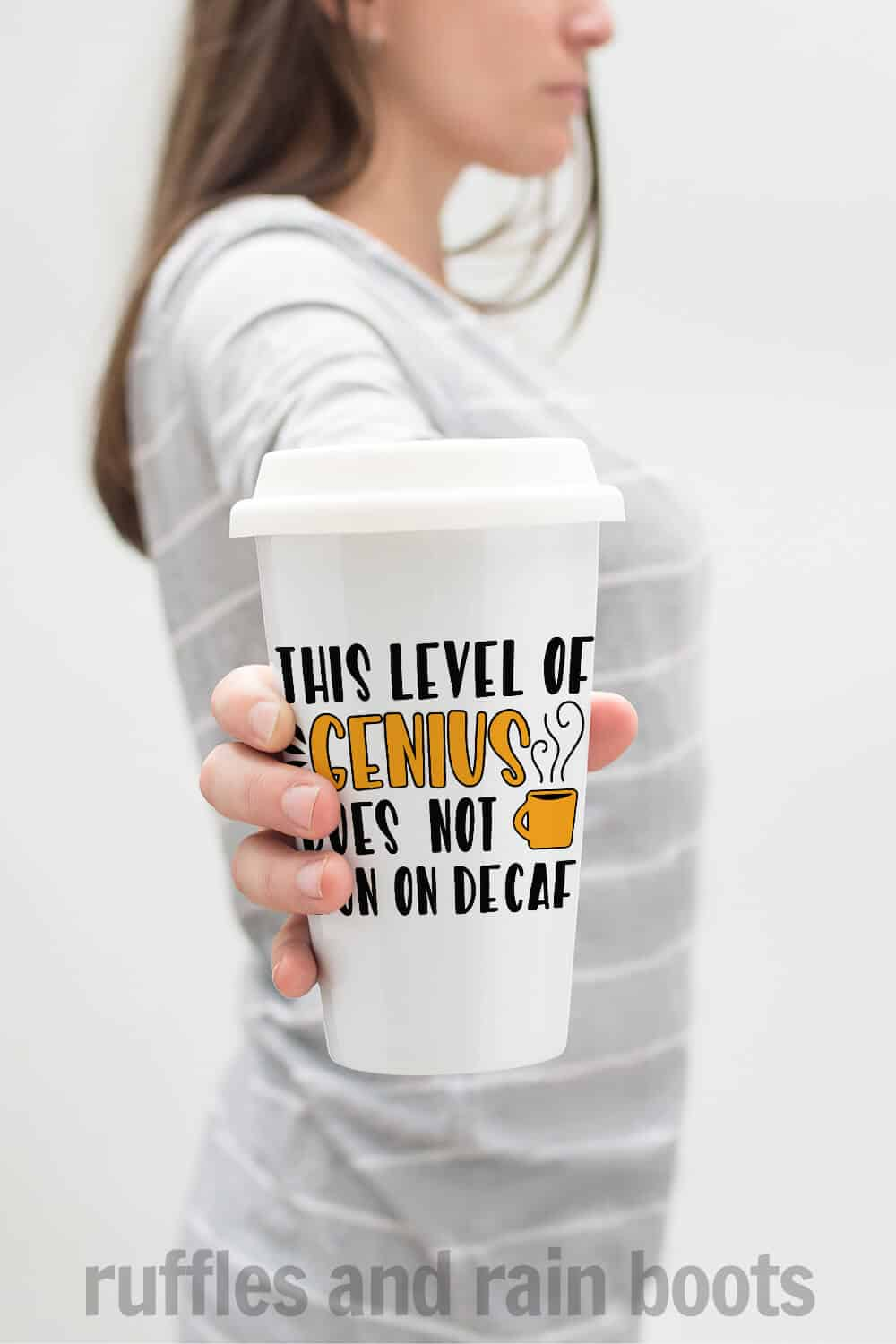 vertical image of a woman in gray holding a white coffee mug with orange and black words which read this level of genius does not run on coffee