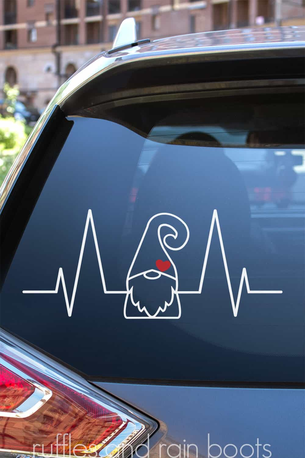 vertical image of the back of a car window with a white gnome heartbeat design