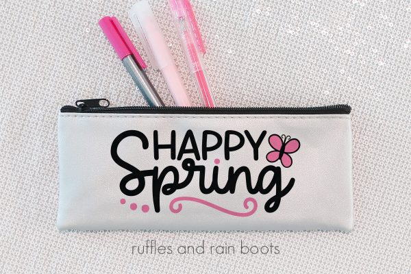 horizontal image of white skinny pen pouch with black and pink lettering in vinyl reading happy spring